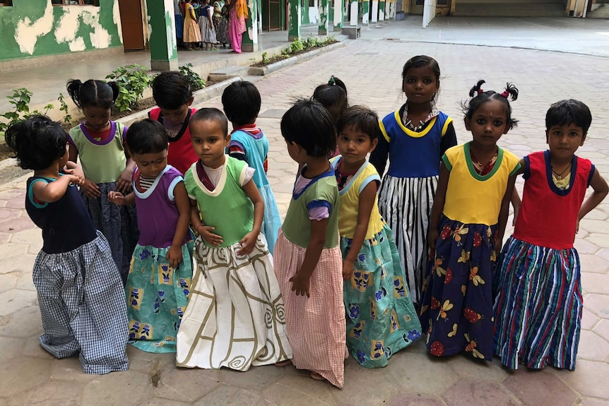 A group of Indian girls in brightly colour dresses gather in front of the camera.