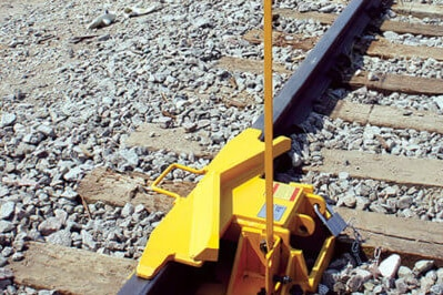 A yellow train derailing device on a track.