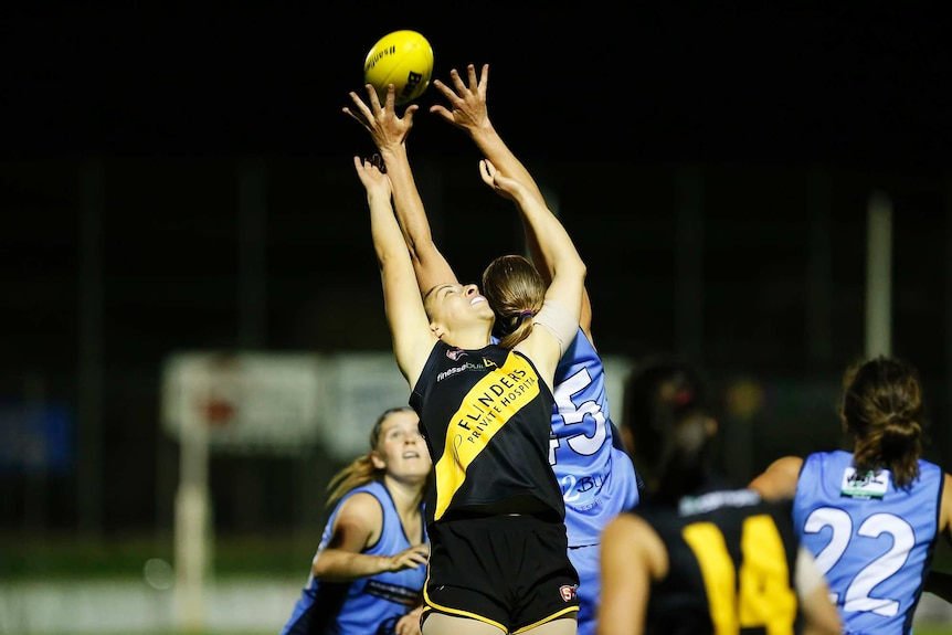 Two female footballers leap for a yellow football.