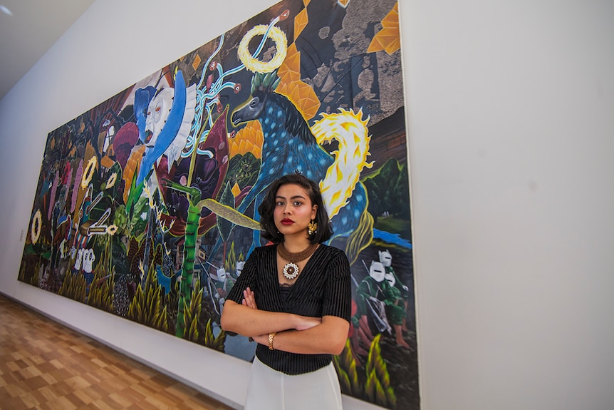 Poet Eunice Andrada stands in front of an acrylic on canvas artwork by Rodel Tapaya at the Art Gallery of New South Wales.