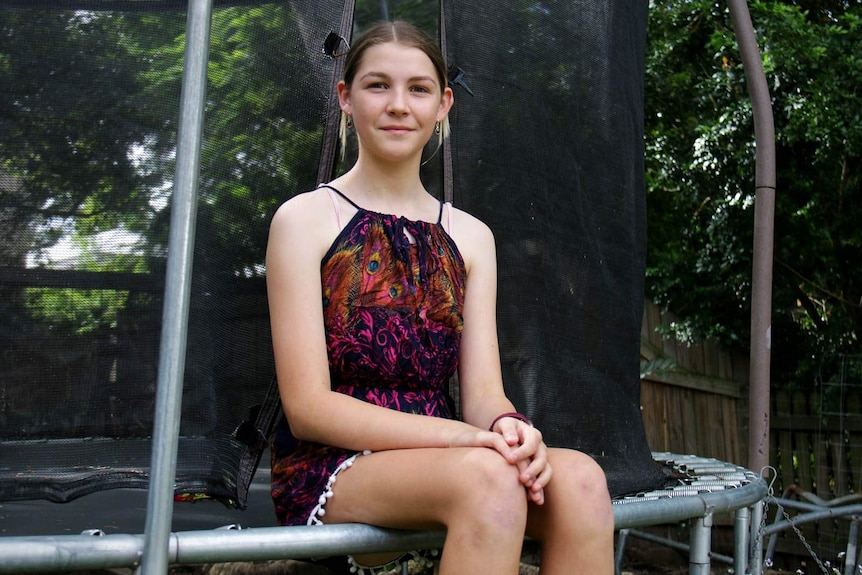 A girl sitting on the edge of a trampoline