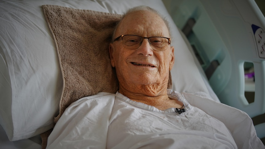 A man lies in a hospital bed and smiles at the camera