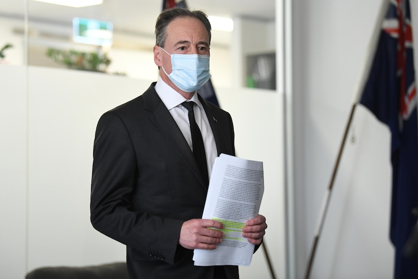 a man wearing a mask and holing onto notes