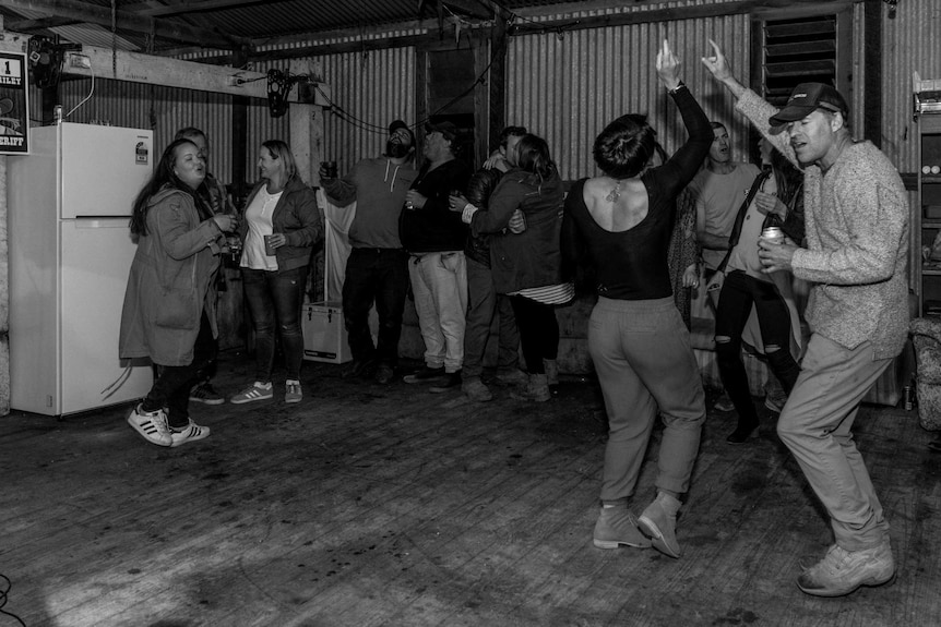 A group of people dancing and partying in a shed with a white fridge in the background