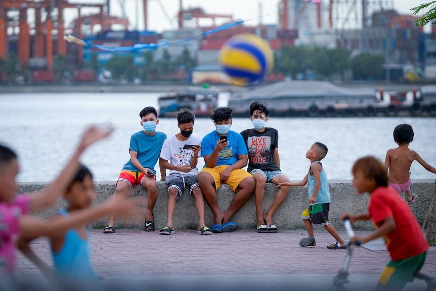 Czterech nastoletnich chłopców siedzi na swoich rówieśnikach, podczas gdy dzieci rzucają przed nimi piłkę