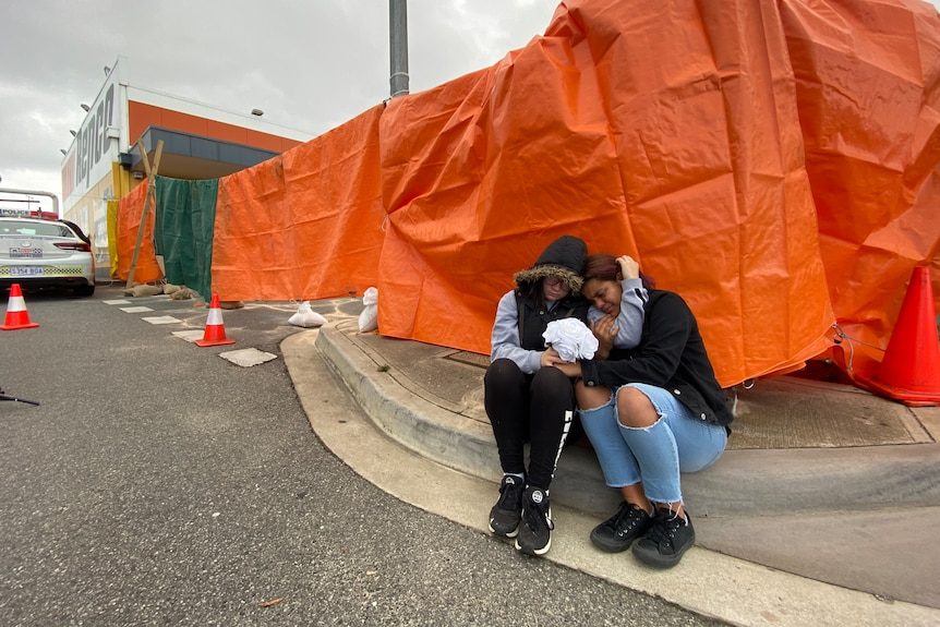 Two young girls embrace as they sit on a curb together