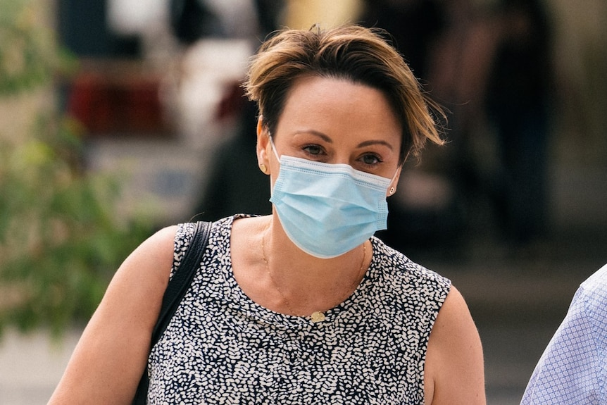 A head and shoulders shot of a woman wearing a floral face mask with her head bowed.