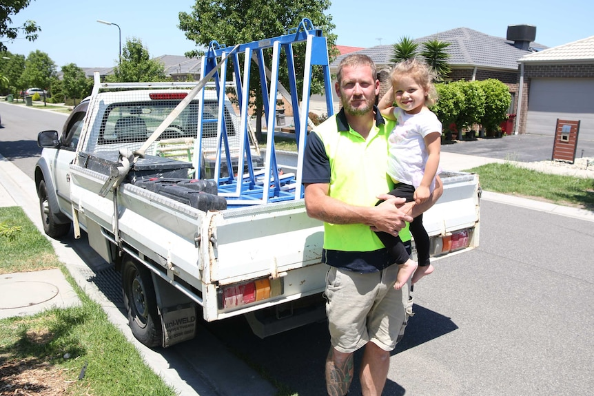 Jack Gray holds his daughter Scarlett in front of a ute.
