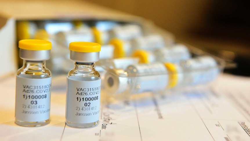 Vials of vaccines sit on top of a medical form