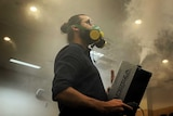 A man holding a smoke machine looks up at the ceiling in an enclosed room.