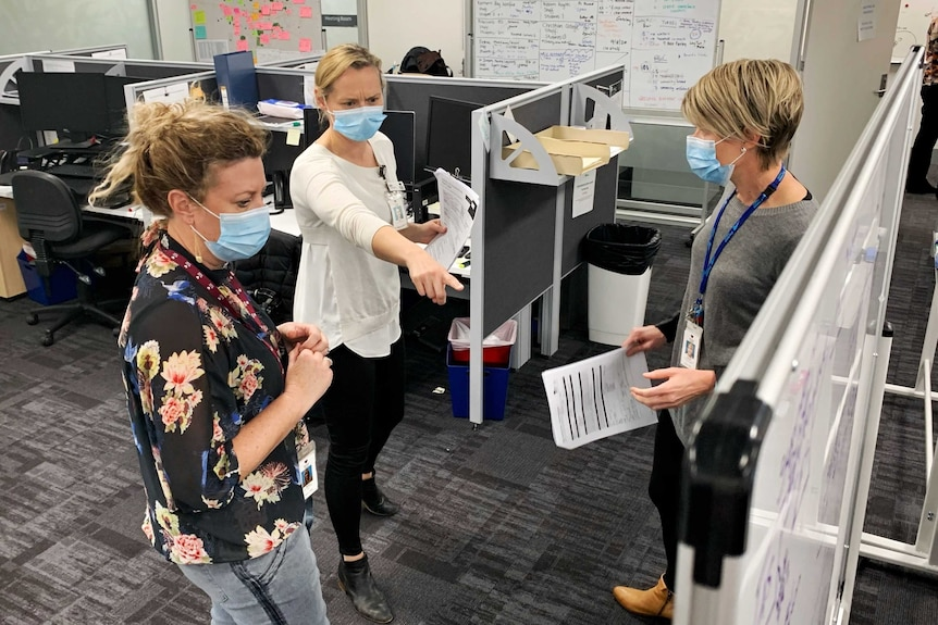 Three women in an office, looking at a whiteboard, one woman points at it, all wearing face masks.