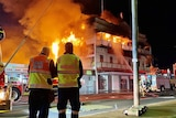 Two fire fighters stand in front of a building on fire