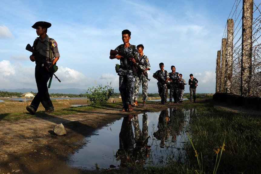 Myanmar police officers patrol along the border fence carrying guns.