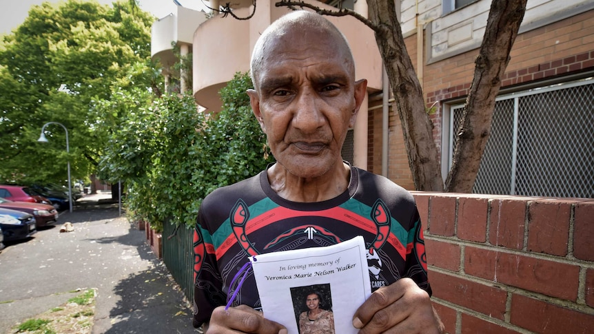 a man holds up a pamphlet with a photo of a woman on it