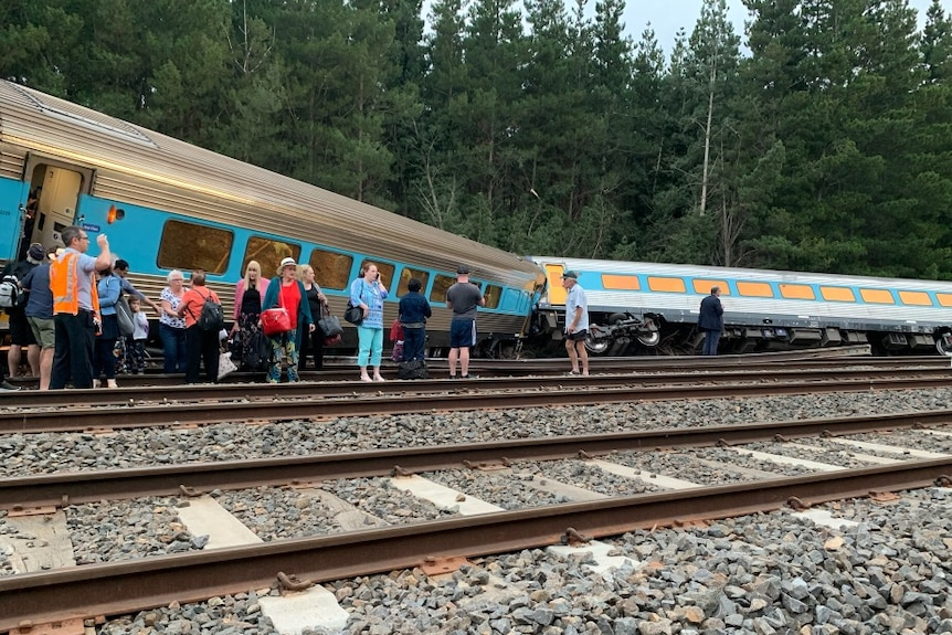 A train derailed and one carriage on its side with passengers standing outside