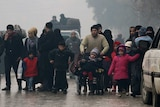 A group of civilians, including women and children, walk down run-down streets of Aleppo.