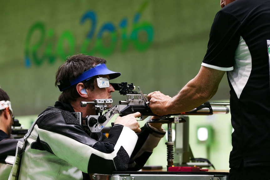 A Paralympic shooter aims his air rifle using a shooting stand.