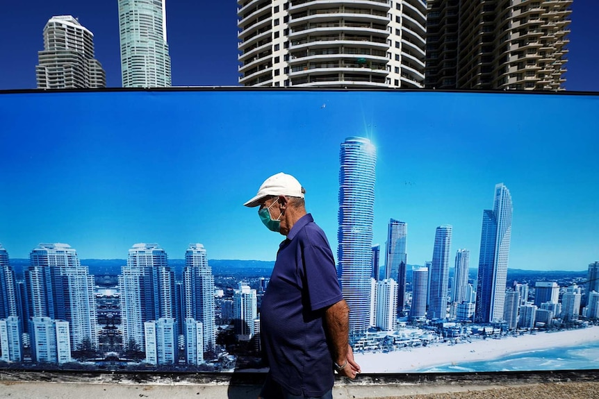 A man wearing a face mask walks past a sign with the Gold Coast skyline on it.