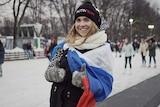 Alexandra Baranova wears a russian flag over her shoulders and a putin team beanie