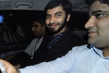 Flown home: Mohamed Haneef (with beard) smiles as he arrives at Brisbane Airport to fly home to India last night.