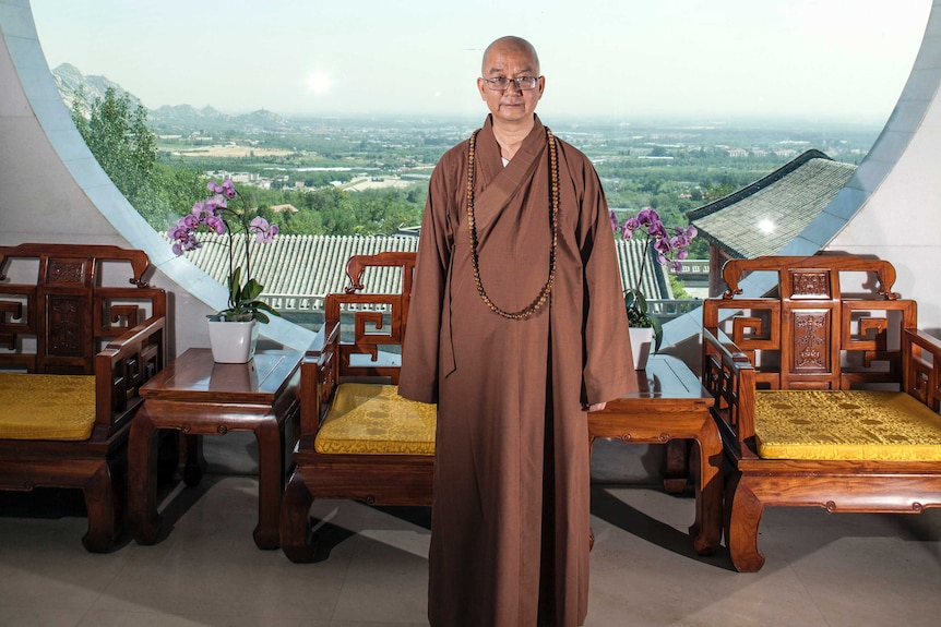 Abbot Xuecheng of the Beijing Longquan Temple. He is posing in front of a window wearing a brown robe and glasses.