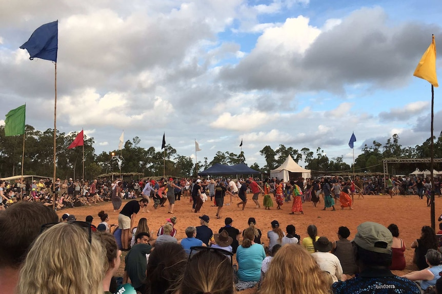 Traditional dancers in modern dress in Arnhem Land are surrounded by a circle of onlookers at the Garma Festival