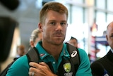 Cricketer David Warner looks serious as he walks through Cape Town International Airport surrounded by media