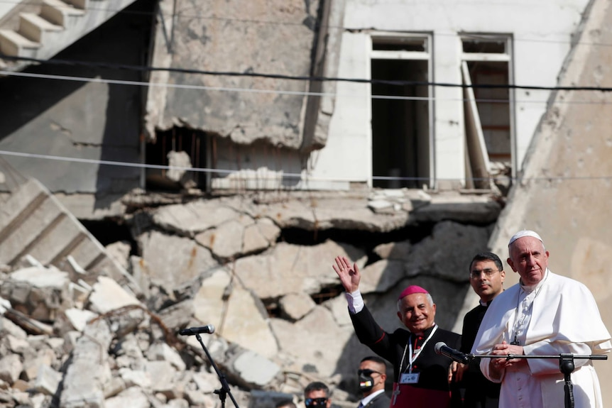 The Pope stands with two Iraqi clerics in front of war-damaged building on a sunny day.