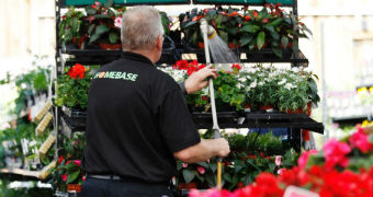 A sales assistant waters plants at a Homebase store in Aylesford.