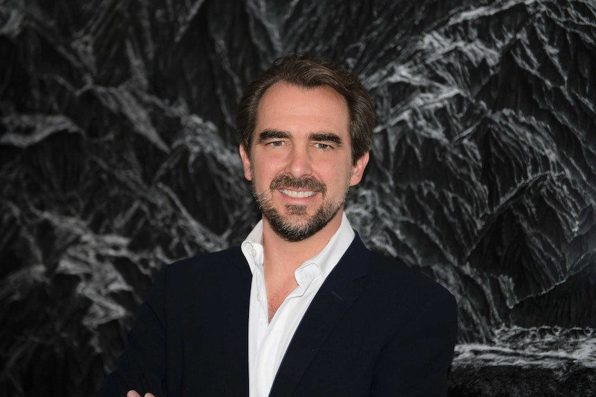 Prince Nikolaos of Greece and Denmark standing in front of one of his photographic artworks.