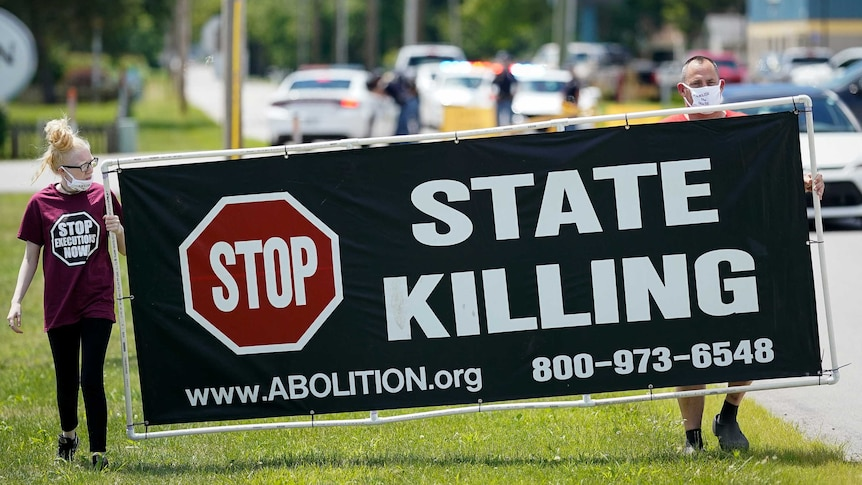 """A woman and a man hold a sign that says """"Stop State Killing""""."""