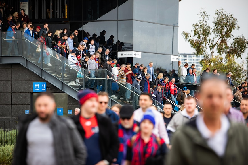 A crowd walking down the stairs at Perth Stadium station.