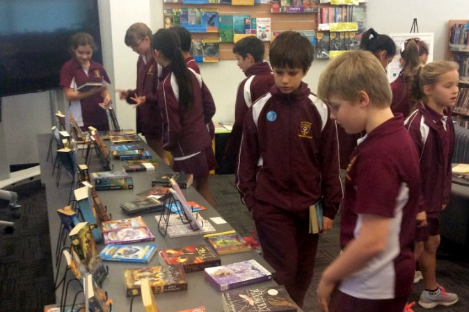 Children look at books on table in school library.