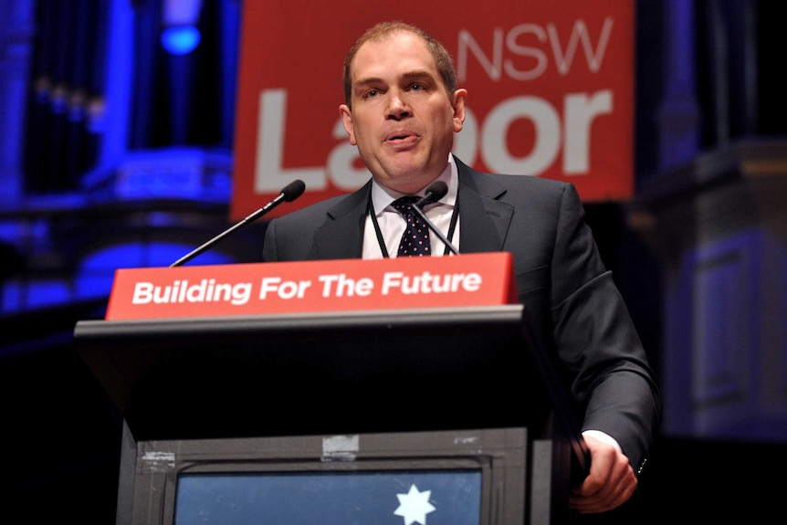 Jamie Clements speaks at a lectern.