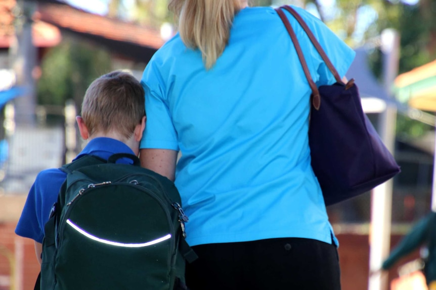 A mother in a blue top walks with her son carrying a green backpack to drop him off at school.