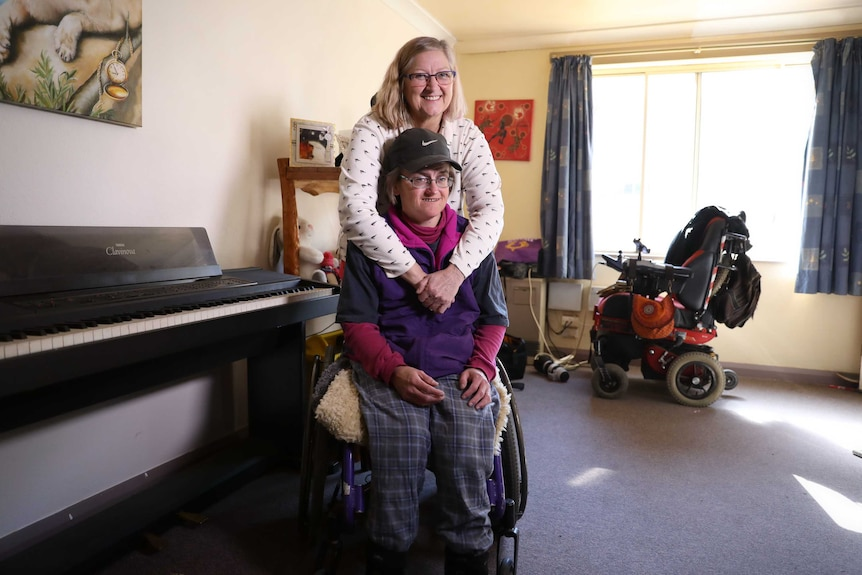 A smiling mother hugs her adult daughter, who is in a wheelchair.