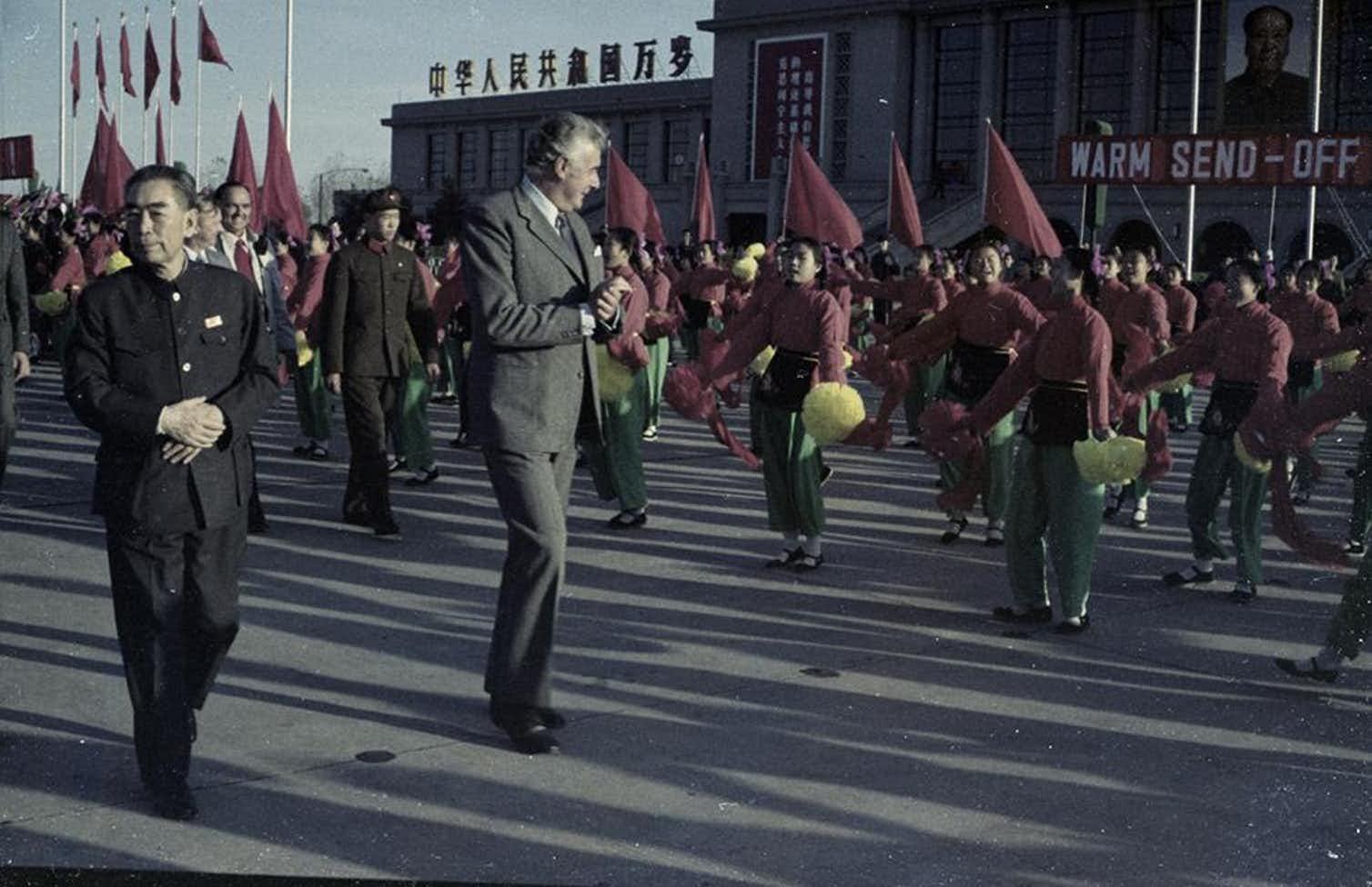Un ritratto del 1973 di Geoff Whitlam e del Primo Ministro Zhou Enlai circondati da una parata di cinesi con in mano delle bandiere