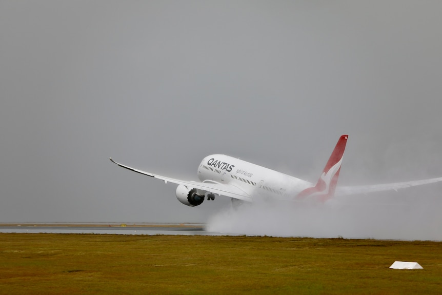 A qantas plane takes off in rainy conditions