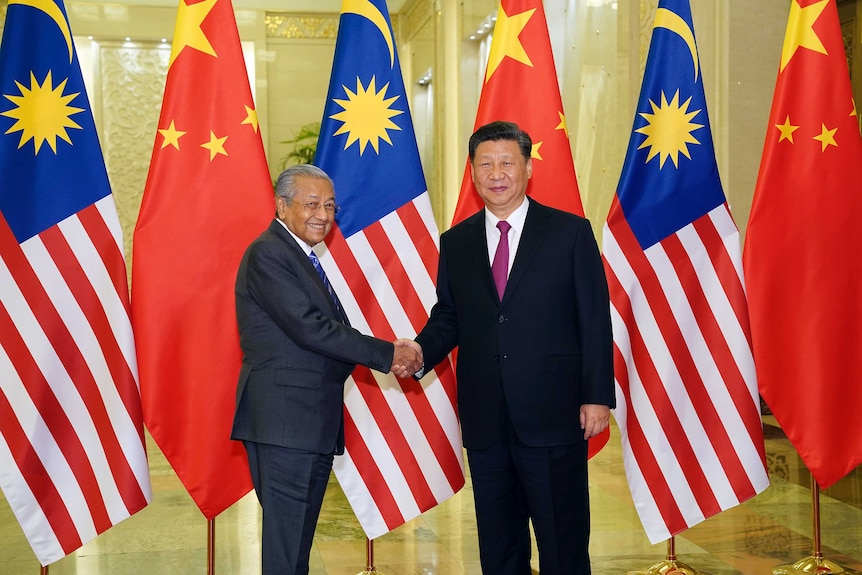 Xi Jinping shakes hands with Malaysian Prime Minister Mahathir Mohamad while standing in front of Malaysian and Chinese flags.