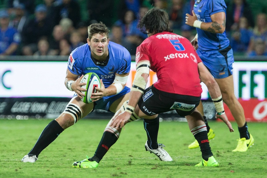 Western Force forward Richard Hardwick carries the ball wearing a blue jersey towards an opponent in red.