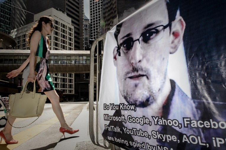 A woman walks past a banner displayed in support of Edward Snowden in Hong Kong