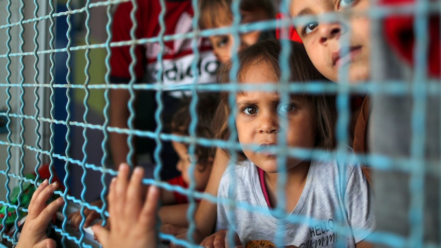 Palestinian children look through a window fence at a United Nations-run school where they take refuge, in Gaza Cityo