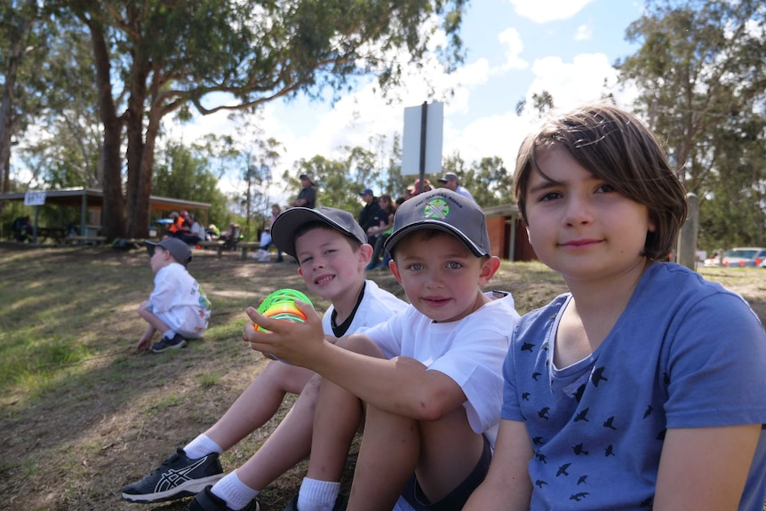 Nina Felmingham, Lochie Strecker and Charlie Henderson watching cricket at a country oval surrounded by trees.