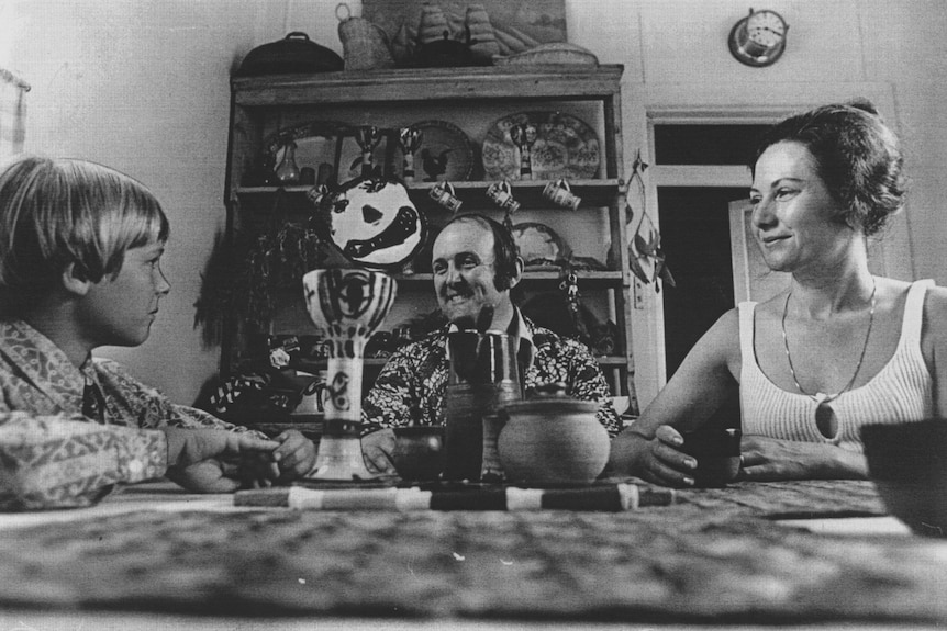 A black and white photograph of a man and woman with their son sitting at dinner table