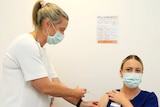 A masked nurse administers a vaccine to another masked nurse in a brightly-lit hospital room.