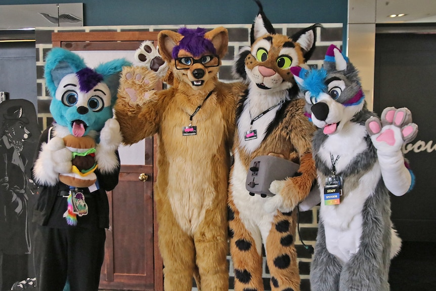 Four people dressed in furry animal costumes with their arms around each other's shoulders