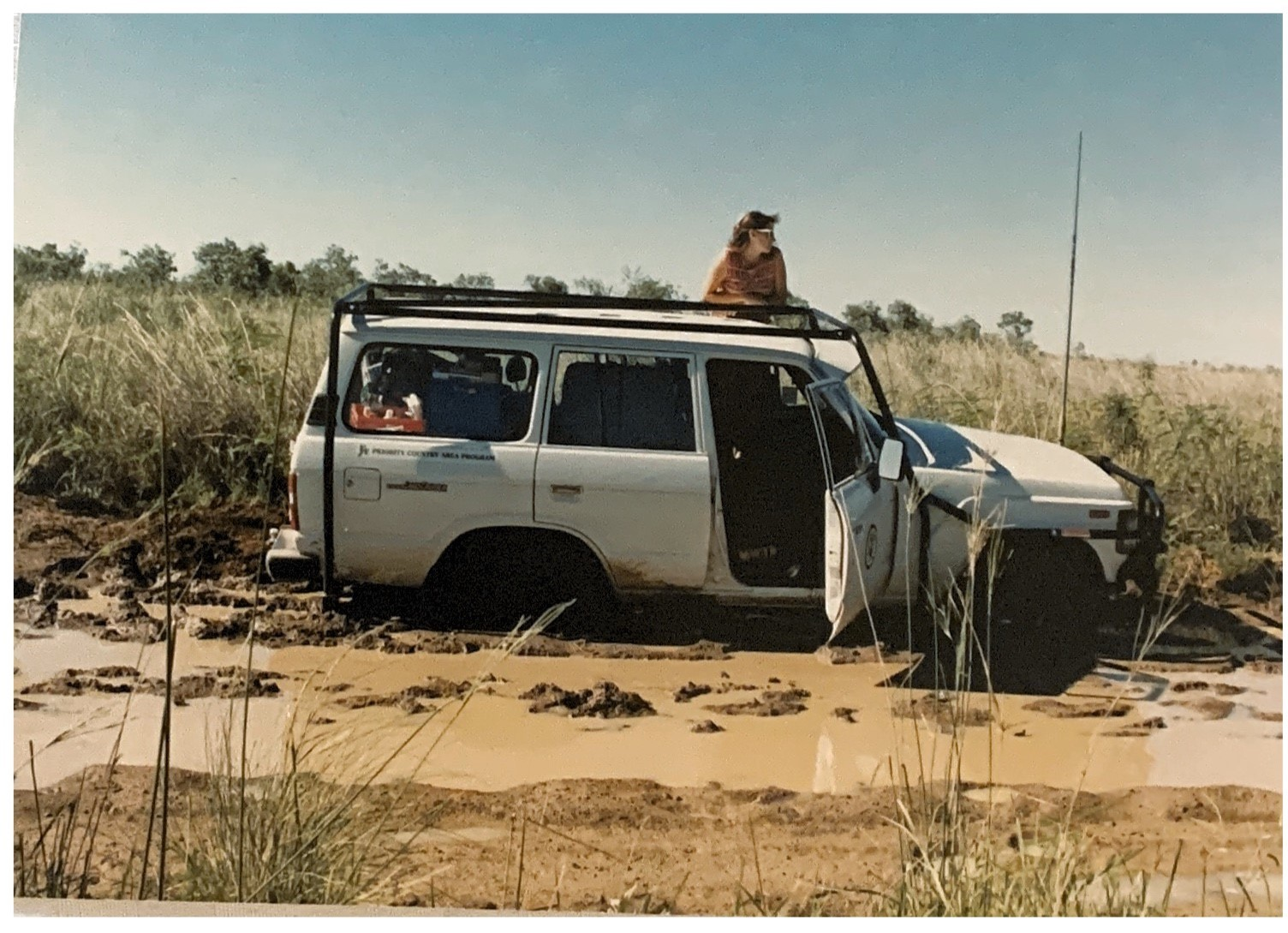 A woman leans out of a bogged car