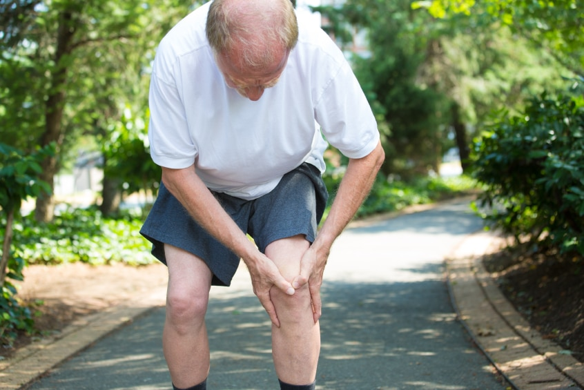 Senior man bent over with knee pain