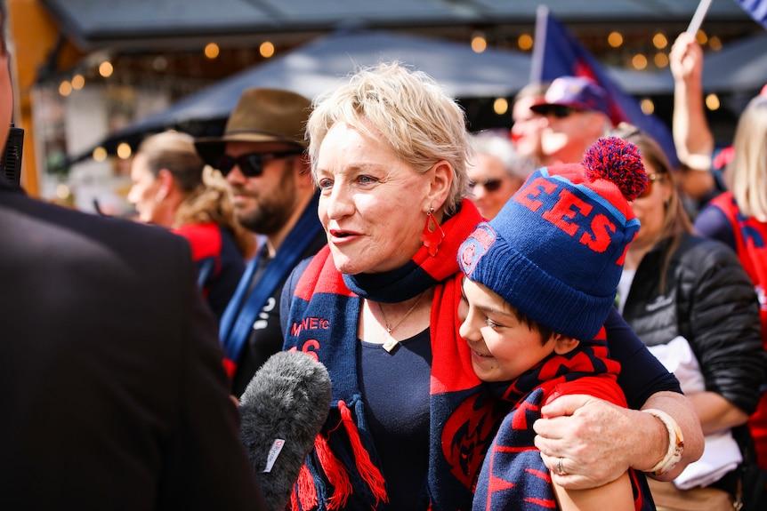 Alannah MacTiernan is interviewed in her Melbourne Demons colours as she hugs a boy
