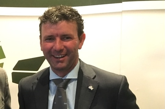A man stands in a suit smiling at the camera